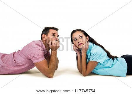 Thoughtful couple laying on floor looking away on white screen