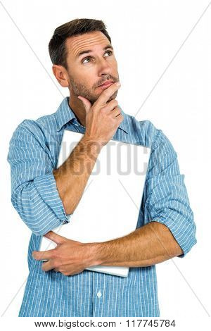Thoughtful man with hand on chin holding laptop on white screen