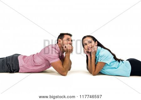 Young couple laying on floor looking away on white screen