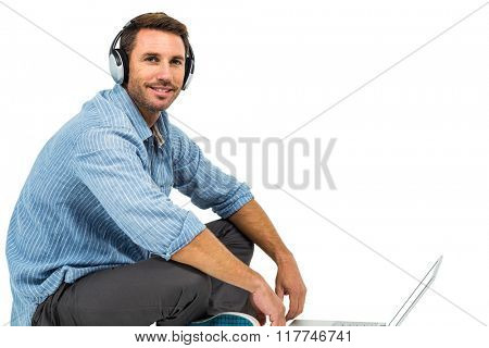 Portrait of man sitting on floor using laptop and headphones on white screen