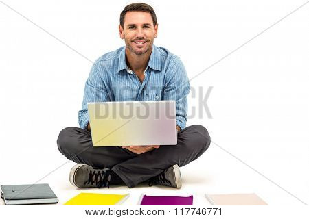 Young man sitting on floor using laptop with notepads on floor on white screen