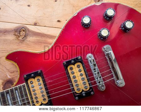 Vintage red guitar on old wood surface.