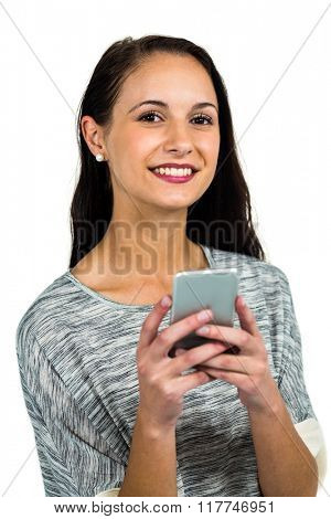 Smiling woman using smartphone and looking at the camera on white screen