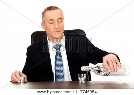 Businessman in office pouring vodka into a glass