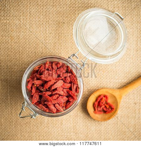 Dry red goji berries in wooden spoon on rustic background.