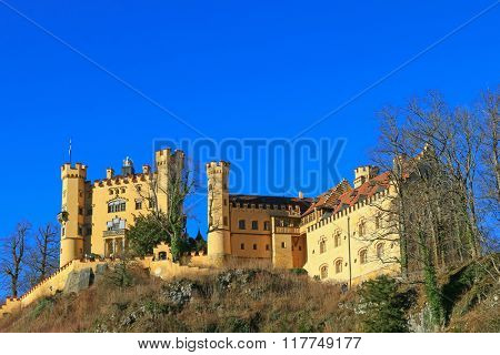 SCHWANGAU, GERMANY - DECEMBER 2015 : The facade of Hohenschwangau Castle on the hill in Schwangau, Germany on December 26, 2015. It is the neo-gothic styled where King Ludwig II. spent his childhood