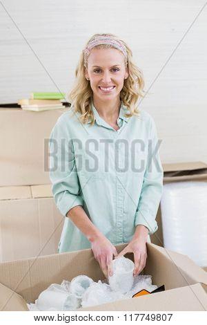 Smiling woman packing mug in a box