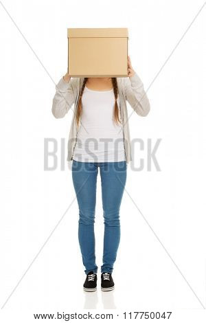 Teen woman covering face with a box.