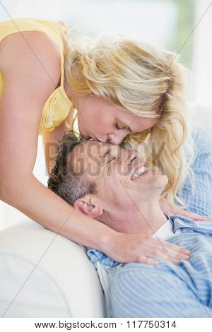 Wife kissing husband on the forehead in the living room