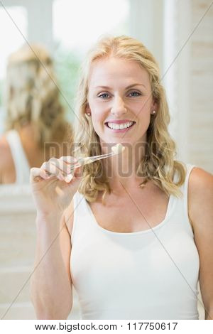 Beautiful woman brushing her teeth in the bathroom