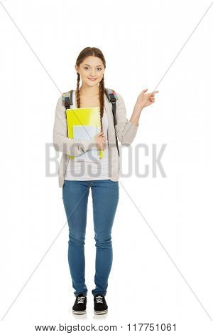 Schoolgirl pointing aside.