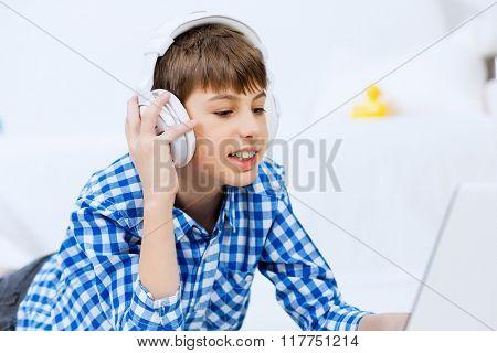 Portrait of little boy listening music from laptop through headphones while lying on hardwood floor