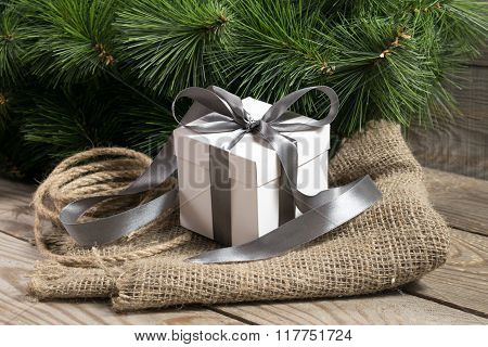 White Gift Box With Grey Ribbons, Cristmas Tree Branch And Rope On Sackcloth On Wooden Background