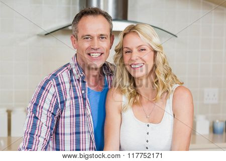 Cute couple looking at camera in the kitchen