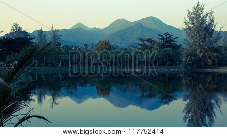Landscape of mountains reflected in the water of the lake, Koh Chang island, Thailand.