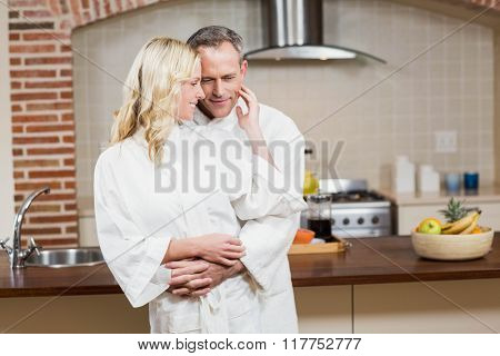 Cute couple cuddling in bathrobe in the kitchen