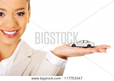 Businesswoman holding small car on palm.