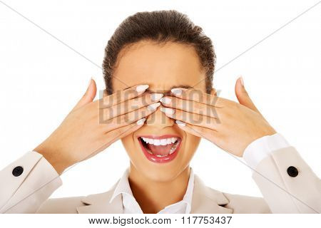 Shocked businesswoman covering eyes with hands.