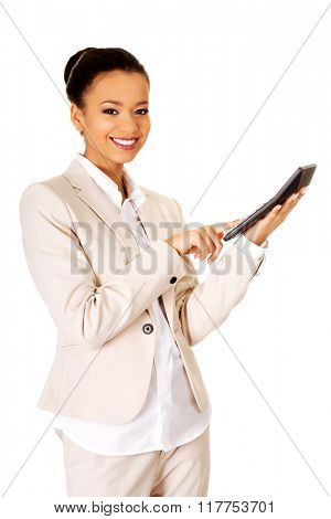 Smiling business woman counting on calculator.