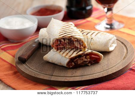 Burritos on a round wooden cutting board