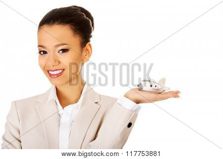 Businesswoman holding small plane on palm.