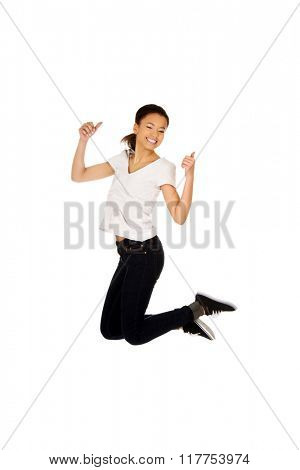 Happy woman jumping with thumbs up.