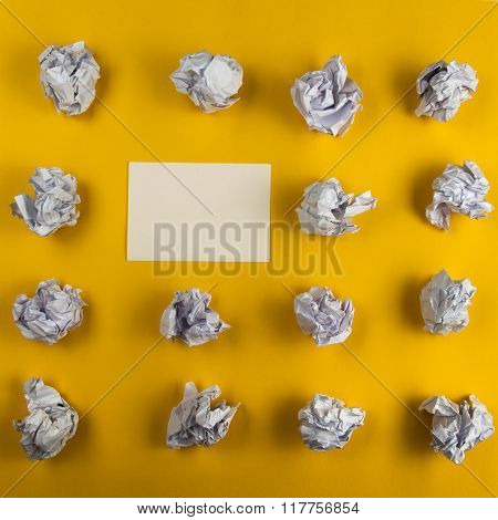 Crumpled paper balls and blank sheet of paper with pencil on yellow background. Paper wad. Creativit