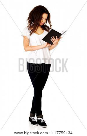 Young student woman reading book.
