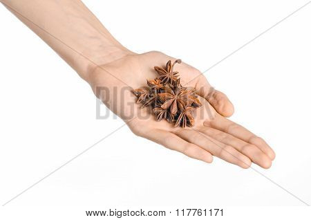 Spices And Cooking Theme: Man's Hand Holding Star Anise Isolated On White Background In Studio