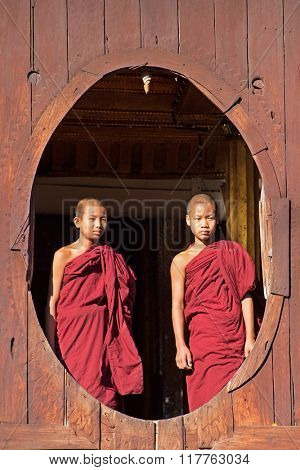 INLE LAKE, MYANMAR - November 24:Young novice monks at window wooden Church of Nyan Shwe Kgua temple near Inle lake on April 22,2014 in Inle lake,Shan State ,Middle of Myanmar.