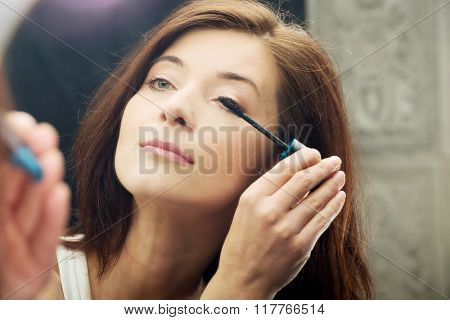 Woman makes light day makeup in bathroom.