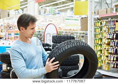 Man Chooses Winter Studded Tires For Car In Supermarket