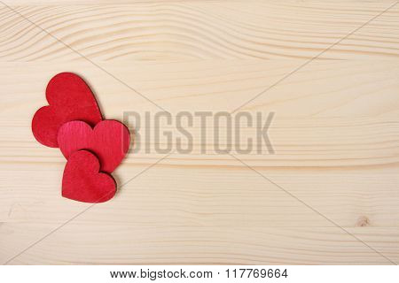 Red wooden Valentine Day hearts on board