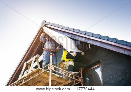 Construction workers thermally insulating house with glass wool and foil.