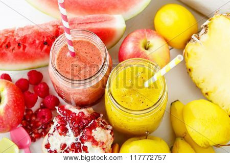 red and yellow smoothie with different fruits and berries