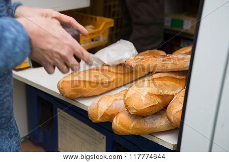 Buying fresh French bread in bakery