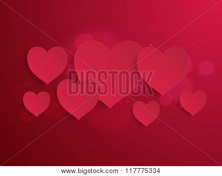 Glossy elegant paper hearts on shiny red background for Happy Valentine's Day celebration.