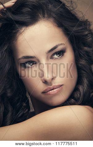 young beautiful woman with dark shiny wavy hair beauty portrait, studio shot, closeup