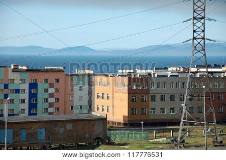 Apartment building block with hilly tundra coast in background Pevek town Chukotka Russia