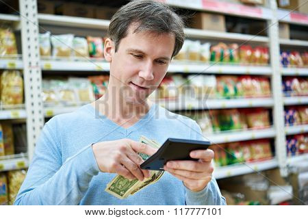 Man With Dollars And Calculator Considers Costs In Store