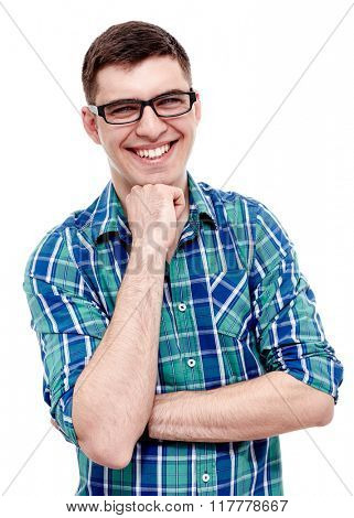Portrait of young man wearing black glasses and blue checkered shirt standing with fist under his chin and laughing isolated on white background - laughter concept