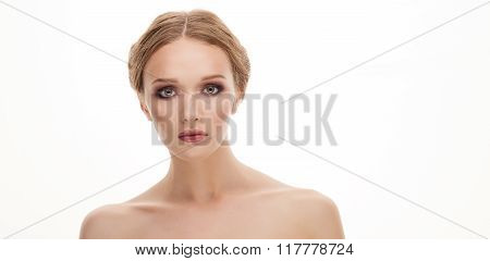 Closeup beauty portrait of young adorable blonde woman showing a cute trendy makeup posing with bare