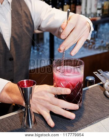 Bartender is stirring a shrub cocktail with sparkling wine