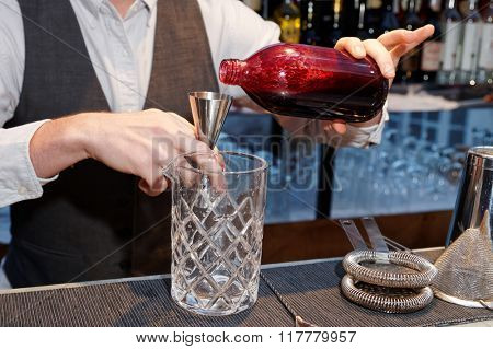 Bartender is pouring black currant shrub in mixing glass