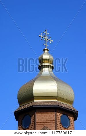 Golden colored dome and cross shaped finial tops the Byzantine Rite Catholic Monastery near Eagle River Michigan.