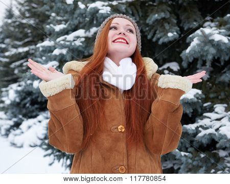 Happy young woman at winter, snowy fir trees background