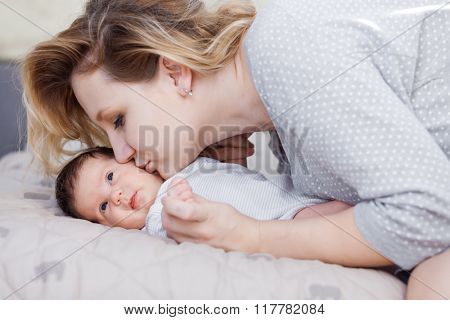 Young mother is kissing her newborn baby