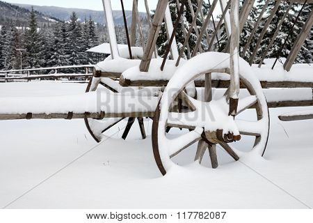 wooden wheel carriage in snow on meadow