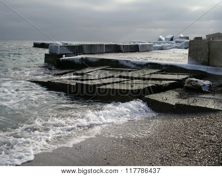 Ice-covered concrete blocks of baffle pier protruding into the sea