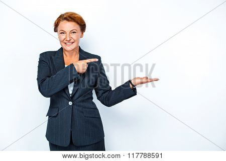 Studio shot of beautiful redheaded business woman. Business woman smiling, looking at camera and pointing aside